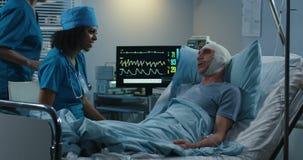 Ärztin, die mit älterem Patienten spricht stock footage