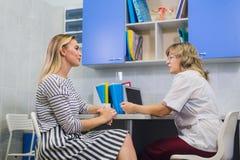 Ärztin, die mit Patienten in Doktorbüro spricht stockfotografie