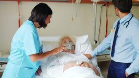 Ärztin, die Sauerstoffmaske auf Patienten setzt stock footage
