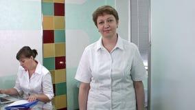 Ärztin, die zur Kamera lächelt und schaut, während ein medizinischer Helfer arbeitet stock footage