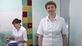 Ärztin, die zur Kamera lächelt und schaut, während ihr Kollege an Laptop arbeitet stock video