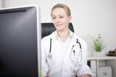 Ärztin in ihrem Büro, das Computer-Monitor gegenüberstellt Stockbild