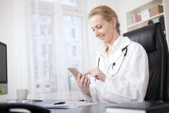 Ärztin an ihrem Tisch grasend an ihrem Telefon Lizenzfreie Stockfotografie