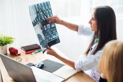 Ärztin im Krankenhaus, das Röntgenfilmgesundheitswesen-, -röntgen-, -leute- und -medizinkonzept betrachtet stockfotos
