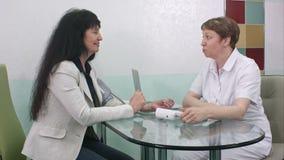 Ärztin im weißen medizinischen Mantelprüfungspatienten-Blutdruck bei der Unterhaltung und dem Sitzen im Büro stock video