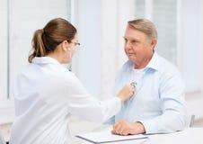 Ärztin mit dem alten Mann, der auf Herzschlag hört stockfotos
