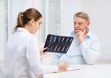 Ärztin mit dem alten Mann, der Röntgenstrahl betrachtet Stockfotos