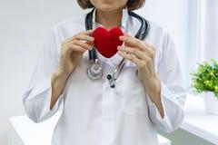 Ärztin mit dem Stethoskop, das Herz, Hintergrundkrankenhausfenster hält lizenzfreie stockfotografie