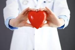 Ärztin mit dem Stethoskop, das Herz in ihren Armen hält Gesundheitswesen- und Kardiologiekonzept in der Medizin lizenzfreie stockfotografie