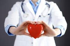 Ärztin mit dem Stethoskop, das Herz in ihren Armen hält Gesundheitswesen- und Kardiologiekonzept in der Medizin stockbild