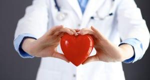 Ärztin mit dem Stethoskop, das Herz in ihren Armen hält Gesundheitswesen- und Kardiologiekonzept in der Medizin lizenzfreie stockbilder
