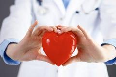 Ärztin mit dem Stethoskop, das Herz in ihren Armen hält Gesundheitswesen- und Kardiologiekonzept in der Medizin lizenzfreie stockfotos