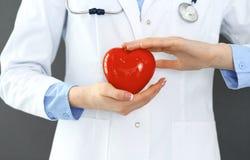 Ärztin mit dem Stethoskop, das Herz in ihren Armen hält Gesundheitswesen- und Kardiologiekonzept in der Medizin lizenzfreies stockfoto
