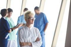 Ärztin mit den Gläsern und blonder Frisur, die im fron stehen Lizenzfreie Stockbilder