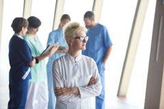 Ärztin mit den Gläsern und blonder Frisur, die im fron stehen Lizenzfreie Stockfotografie
