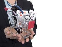 Ärztin mit schwarzem Anzug hält kleinen Warenkorb mit bunten Pillen, Injektionsspritze und Stethoskop Stockfotos