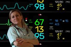 Ärztin- oder Krankenschwesteraufenthalt in der Uniform mit Stethoskop und Blicke auf das Kameralächeln Elektrokardiogrammschirmmo lizenzfreie stockfotografie