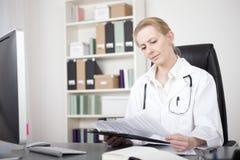 Ärztin Reading Medical Reports in ihrem Büro Lizenzfreie Stockfotos