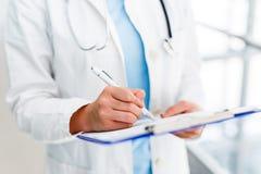 Ärztin schreibt auf Pappe Stockfotos