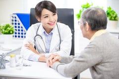 Ärztin sehen älteren Patienten stockfotos