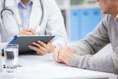 Ärztin sehen älteren Patienten lizenzfreie stockfotografie