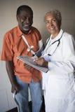 Ärztin-Standing With Disabled-Patient stockfotos