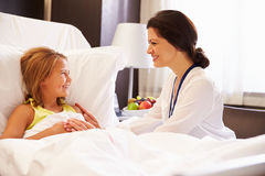 Ärztin-Talking To Child-Patient im Krankenhaus-Bett Stockbild