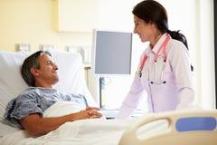Ärztin-Talking To Male-Patient im Krankenhauszimmer stockfotos