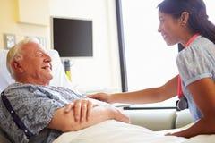 Ärztin-Talking To Senior-Mann im Krankenhauszimmer lizenzfreie stockfotos