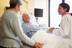 Ärztin-Talking To Senior-Paare im Krankenhauszimmer lizenzfreies stockfoto