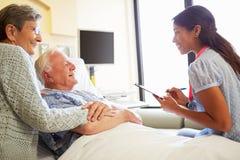 Ärztin-Talking To Senior-Paare im Krankenhauszimmer lizenzfreie stockfotografie