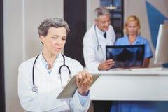 Ärztin unter Verwendung der digitalen Tablette mit dem Kollegen, der Röntgenstrahl überprüft Stockfoto
