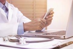 Ärztin unter Verwendung des intelligenten Mobiltelefons Stockfotos