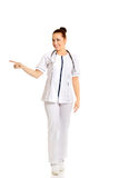 Ärztin in voller Länge, die nach links zeigt Stockbilder