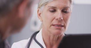 Ärztin von mittlerem Alter, die eine Tablette betrachtet Stockfotos