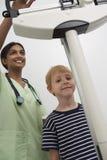 Ärztin Weighting Young Patient stockfoto