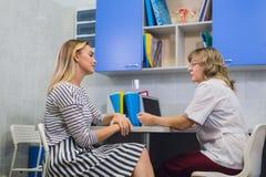 Ärztingynäkologe mit Patienten in ihrem Büro stockfoto