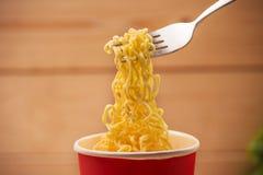 Äta ögonblickliga nudlar i kopp med en gaffel Arkivfoto