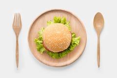 Äta bbq-hamburgaren på trämaträtten som isoleras på vit bakgrund arkivfoto
