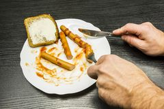 Äta bestick med lagade mat korvar, med ketchup och en skiva med smör för frukost royaltyfri fotografi