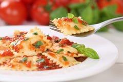 Äta den italienska pastaraviolit med mål för nudlar för tomatsås arkivfoto