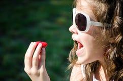 äta den klara jordgubben till Arkivbild