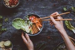 Äta den läckra asiatiska bunken med risnudlar, grönsaker och till royaltyfria bilder