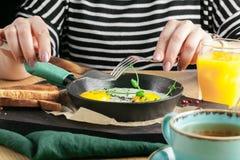 Äta den läckra frukosten för restaurang med den soliga sidan upp stekte ägg, bacon, grönsaker och gräsplaner royaltyfria foton