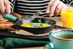 Äta den läckra frukosten för restaurang med den soliga sidan upp stekte ägg, bacon, grönsaker och gräsplaner arkivbilder