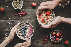 Äta den läckra smoothien för den helthy frukosten bowlar med frukter, bär och frö på träbakgrunden arkivfoto