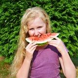 äta den lyckliga vattenmelonen för flicka Fotografering för Bildbyråer