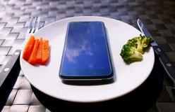 Äta den smarta telefonen på maträtt arkivbilder