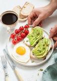 Äta den sunda frukosten med avokadot, ägget, rostat bröd och kaffe arkivbild