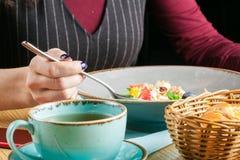 Äta den sunda frukostkvinnan som äter havremjöl i kafé royaltyfri bild